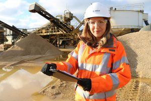 photo showing apprentice Izzy Bowles with hard hat, fluorescent jacket and clipboard in hand with machinery and materials in the background