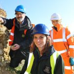 Photo shows three people in the foreground of a quarry as part of a restoration project